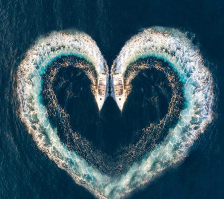 Zwei Motorboote zeichnen ein Herz aus Luftblasen auf dem Meer; Luftaufnahme