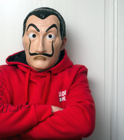 """Mulhouse -  France - May 16 2020 : Portrait of fan of the serie tv """"La casa de papel (paper house) traduction in english on Netflix standing with red sweat shirt costume and Salvador Dali mask"""