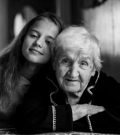Elderly woman portrait with her granddaughter, black and white photo.