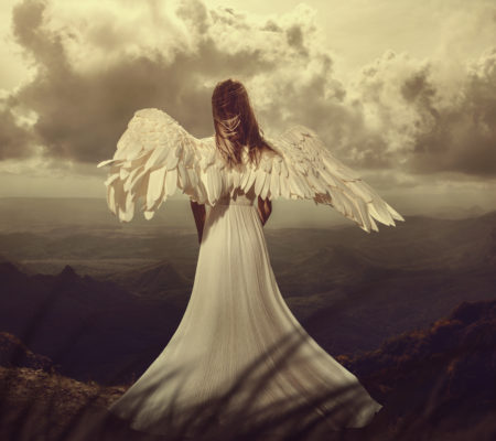 Back view of a woman with wings looking on horizon of mountains. angel
