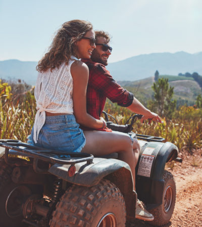 Portrait of young man and woman in nature on a off road vehicle. Young couple enjoying a quad bike ride in countryside.