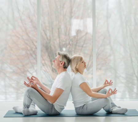 Harmony and calm. Beautiful senior couple doing yoga together in the white gym with panoramic windows. Health and sport concept. Copy space.