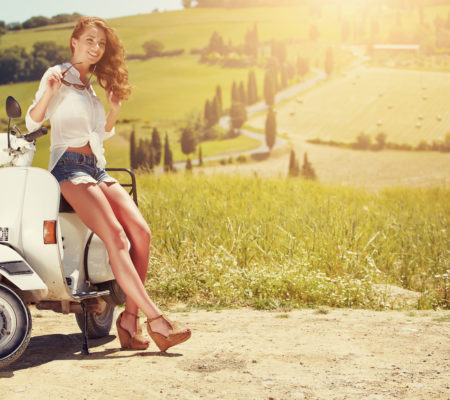 Portrait of summer girl on scooter - Outdoor on Tuscany hiills.Retro shot. Vintage photo