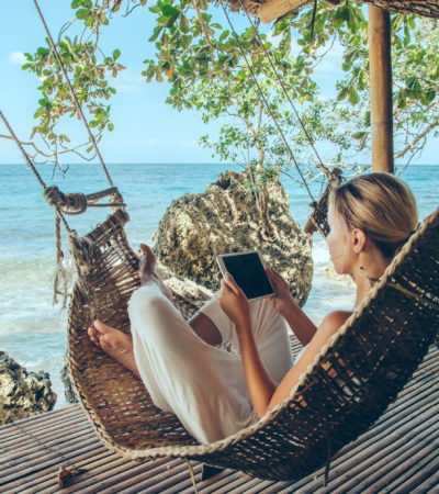 Woman working with tablet pc while relaxing in the hammock on tropical beach in hot sunny day